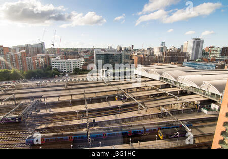 Leeds, England - June 28, 2015: Looking across waiting trains at the platforms of Leeds Railway Station to the skyline - Stock Photo