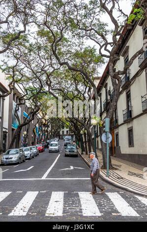 Elderly poeple crossing a city road using the Zebra crossing. - Stock Photo