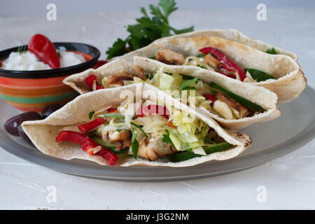 Pita filled with grilled chicken fillet, fresh salad, cucumber, sweet paprika, onion and yoghurt sauce on a white - Stock Photo