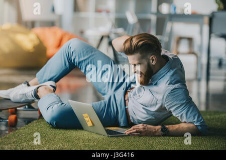 Smiling bearded man lying on floor and using laptop in creative office - Stock Photo