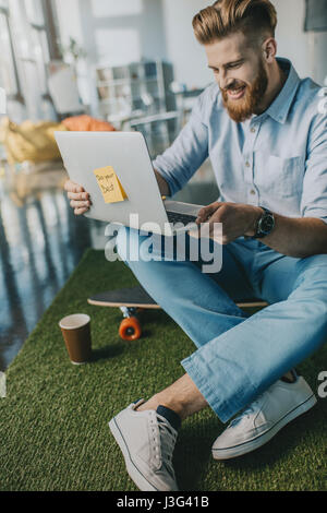Smiling bearded man sitting on skateboard and using laptop - Stock Photo