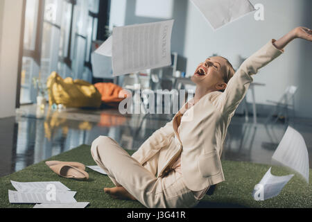 Excited young businesswoman throwing documents while sitting on floor in office - Stock Photo