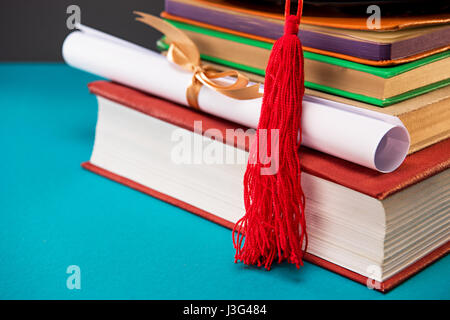 close up of books, diploma and graduation cap with tassel on blue, education concept - Stock Photo