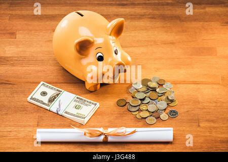 diploma and piggy bank with coins and dollars on wooden tabletop, education concept - Stock Photo