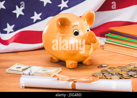 diploma and piggy bank with coins and dollars usa flag behind, education concept - Stock Photo