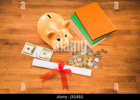 diploma, books and piggy bank with coins and dollars on wooden tabletop, education concept - Stock Photo