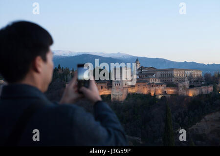 Asian tourist uses his smartphone to photograph the Alhambra Palace from the Mirador de San Nicolas in El Albayzin - Stock Photo