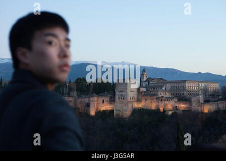 Asian tourist in front of the Alhambra Palace pictured from the Mirador de San Nicolas in El Albayzin district in - Stock Photo