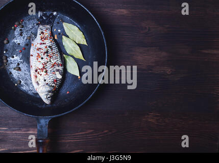 Carp fish in spices on a black cast-iron frying pan, empty space on the right - Stock Photo