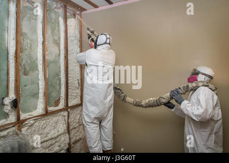 Workers Spraying Open Cell Foam Insulation On Interior Walls Of Home - Stock Photo