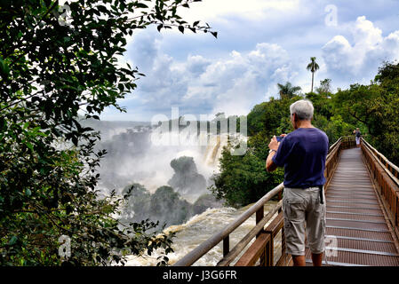 Senior man tourist taking a picture of a Iguazu Falls (aka Iguassu Falls or Cataratas del Iguazu), Misiones Province, - Stock Photo