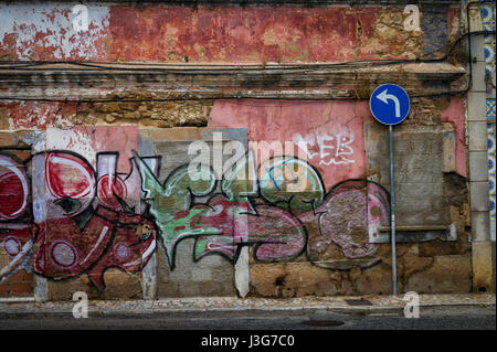 left turn street sign against an old abandoned building covered with graffiti. - Stock Photo