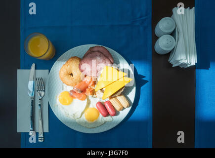Delicious breakfast with fried eggs, sausage, sandwichs and orange juice - Stock Photo