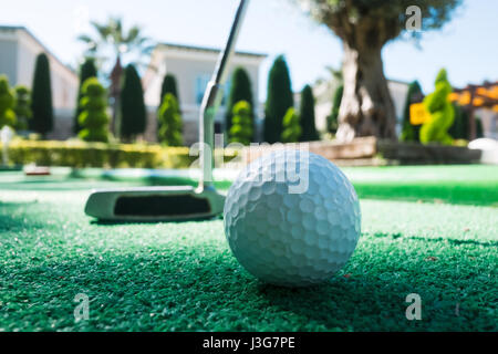 Mini golf scene with ball and club. Sunny day at resort park - Stock Photo