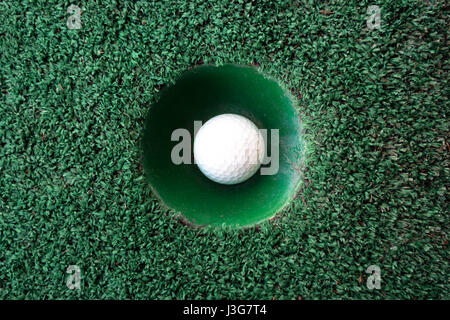 Mini golf scene with ball and hole. Can be used like background. Sunny day at resort park - Stock Photo