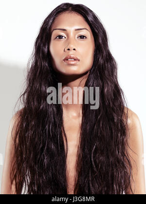 Expressive artistic beauty portrait of a beautiful young exotic woman with very long wavy brown hair, front view - Stock Photo