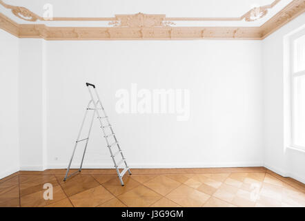 ladder in empty room with white wall and wooden floor - Stock Photo