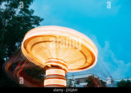 Top Disk Part Of Brightly Illuminated, Dynamic Energy Rotating High Speed Carousel Merry-Go-Round With Blurred Motion - Stock Photo