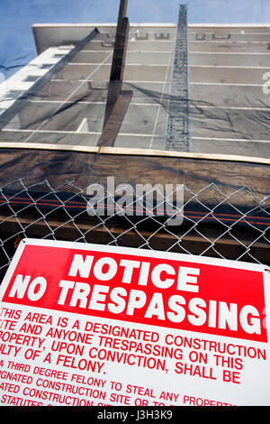 Miami Beach Florida Ocean Drive building construction site fence sign no trespassing warning felony theft notice - Stock Photo