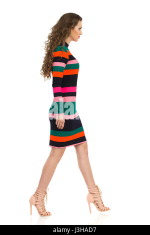 Serious beautiful young woman in colorful striped mini dress and high heels is walking. Side view. Full length studio - Stock Photo