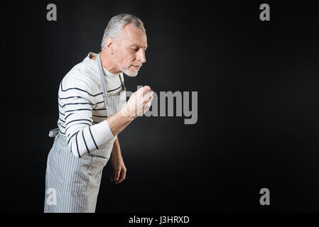 From me with love. Delighted bearded gray-haired man wrinkling forehead standing in profile over black background - Stock Photo