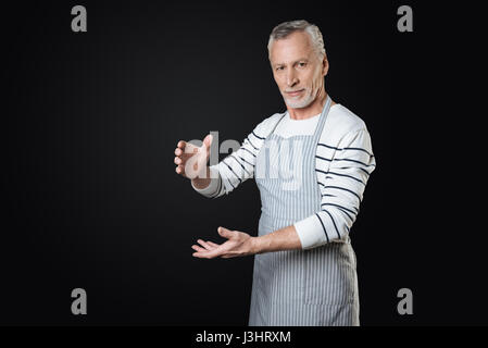 I have it. Delighted bearded gray-haired man wearing striped apron looking straight at camera standing over black - Stock Photo
