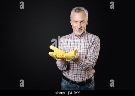 Take it. Delighted bearded gray-haired man wearing gloves looking straight at camera standing over black background - Stock Photo