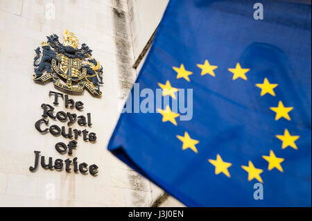 EU European Union flag flying in bright sun in front of the Royal Courts of Justice public building in London, United - Stock Photo
