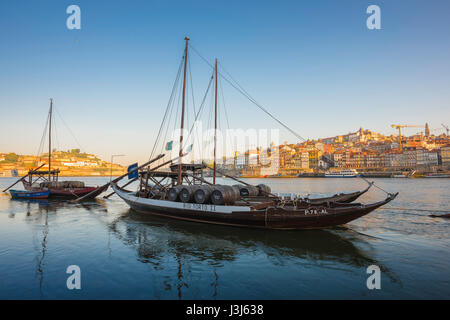 Porto Douro river, traditional rabelo boats on the Douro River with the skyline of Porto at sunrise in the background, - Stock Photo