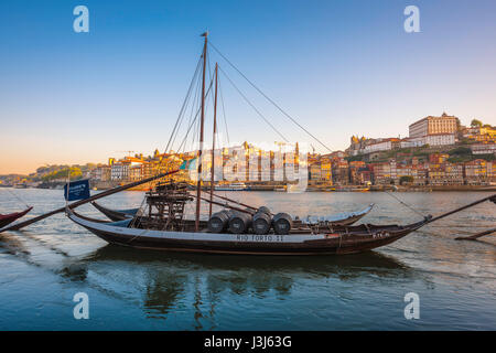 Douro Porto Portugal, a traditional rabelo boat on the Douro River with the skyline of Porto at sunrise in the background, - Stock Photo