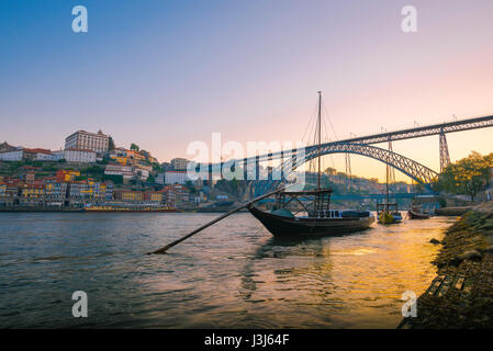 Douro Porto Portugal, a traditional rabelo boat on the Douro River with the skyline of Porto at dawn in the background, - Stock Photo