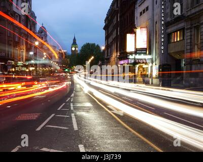 Light trails from cars and buses at Trafalgar Square, London, UK. Night time - Big Ben in background - Stock Photo