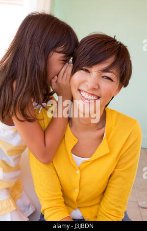Mother and daughter laughing and telling secrets. - Stock Photo