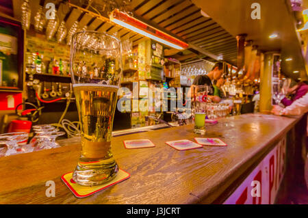 BRUSSELS, BELGIUM - 11 AUGUST, 2015: Glass of beer sitting on bar counter inside Delirium Bar, selection of other - Stock Photo