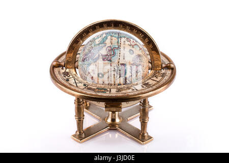 Vintage world globe on a brass stand on a white surface. Antique world globe isolated on white background. - Stock Photo