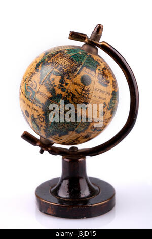 Vintage world globe on a wooden stand on a white surface. Antique world globe isolated on white background. - Stock Photo