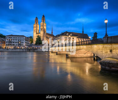 Grossmunster Church and Limmat River in the Evening, Zurich, Switzerland - Stock Photo