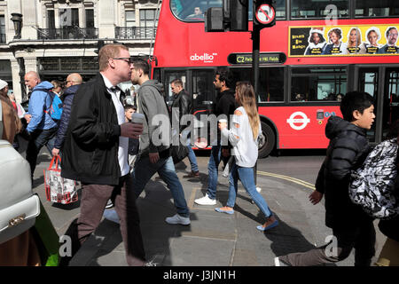 Pedestrians and shoppers walking along Regent Street with red double-decker bus in spring 2017, West London W1B, - Stock Photo