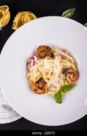 Seafood. Shellfish. Pasta with grilled prawns shrimps, with tomatoes, fresh herbs basil and spices - Stock Photo