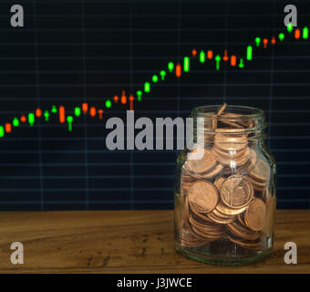 golden coins jar  on the financial stock charts as background. - Stock Photo