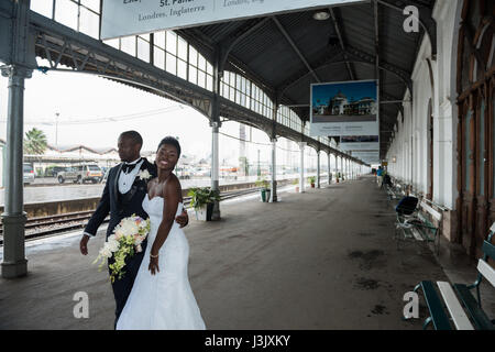 A newly wed couple take shelter from the rain at the historic Caminho de Ferro de Mocambique Maputo railway station - Stock Photo