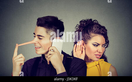 Curious worried woman secretly listening to a happy man liar talking on mobile phone with his lover isolated on - Stock Photo