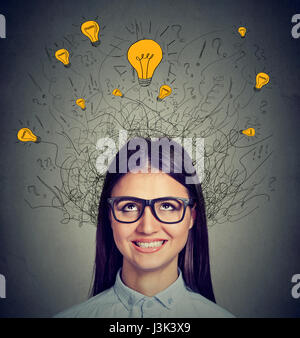 Young woman with many ideas light bulbs above head looking up isolated on gray wall background. Eureka concept - Stock Photo
