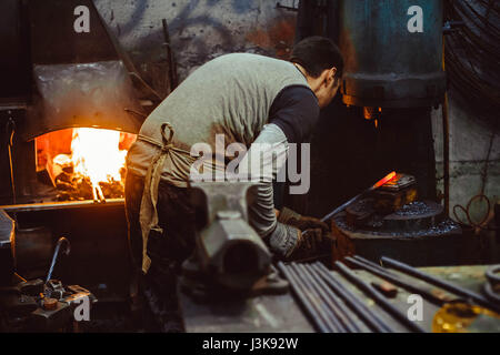 blacksmith working in the forge on auto hammer - Stock Photo