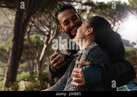 Loving young couple camping in forest and having coffee. Young man and woman sitting together outdoors and smiling. - Stock Photo