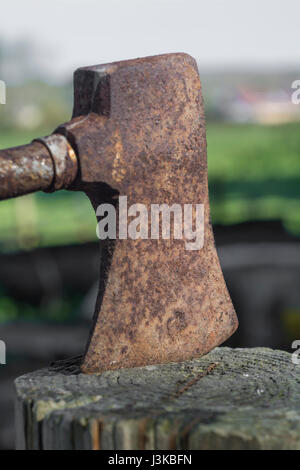 Old rusty axe embedded in wooden block - as visual metaphor for job cuts, unemployment, tax cuts, & so on, also - Stock Photo