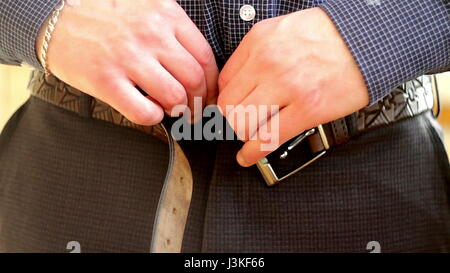 Man in blue shirt buckling undoes the belt on his pants. - Stock Photo