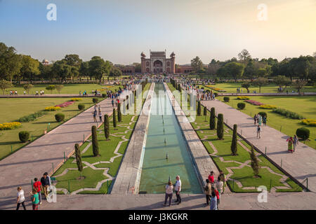 Taj Mahal garden with tourists and red sandstone built Mughal architectural East gate as viewed from the top of - Stock Photo