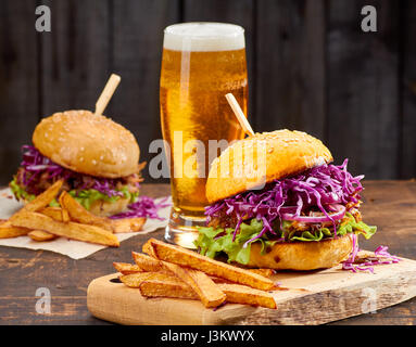 Two sandwiches with pulled pork, french fries and glass of beer on wooden background - Stock Photo