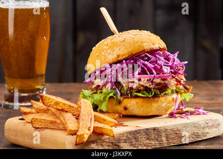 Sandwith with pulled pork and french fries on wooden background - Stock Photo